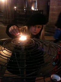 girl lighting a candle in Notre Dame