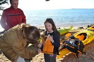 teen helping sister get ready to kayak