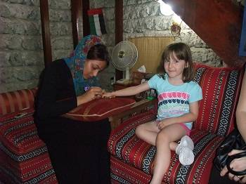 girl having henna done at Dubai museum