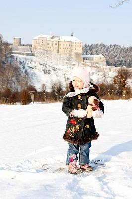 girl with Cesky Sternberk Castle in winter at background, Czech Republic