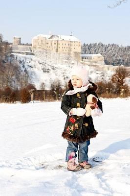 girl with Cesky Sternberk Castle in winter at background, Czech Republic