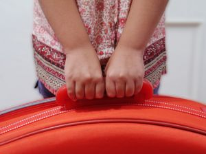 child holding a suitcase
