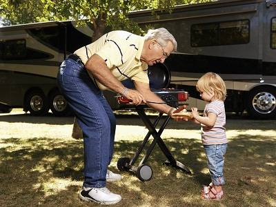 Grandfather BBQing with child at an RV stop