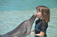 young girl kissing a dolphin at Atlantis
