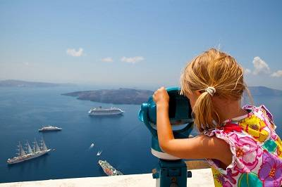 Young girl looking at cruiseships inSantorini, Greece